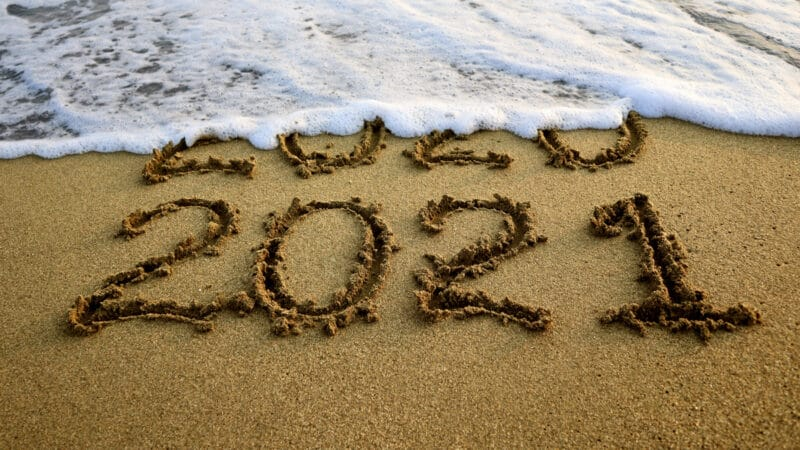 New year 2021 and 2020 on sandy beach with waves
